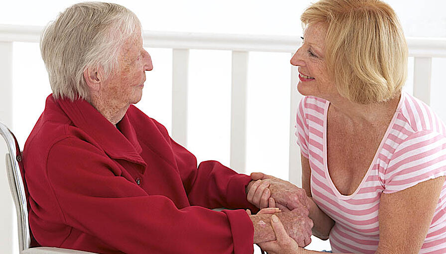 Elderly woman holding hands and talking