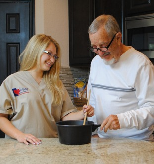 Caregiver Stirring a Pot With Senior Male during meal preparation