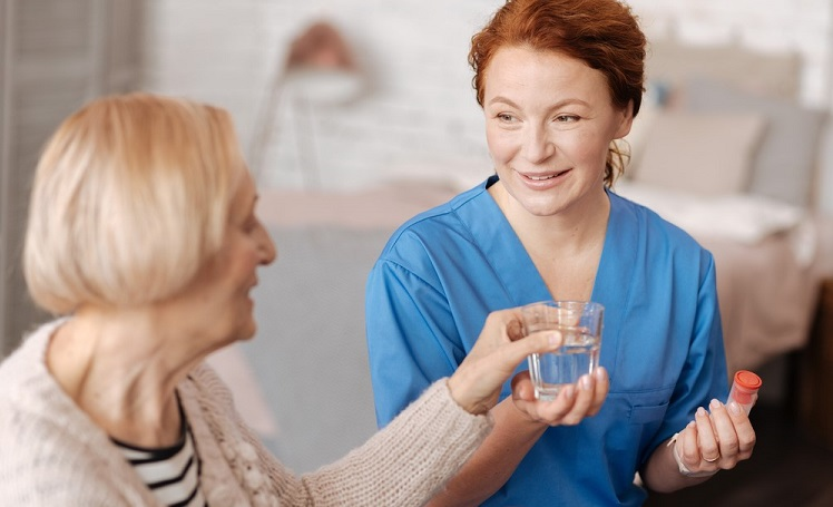 Caregiver helping a senior woman take medication