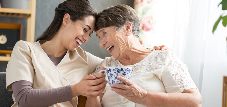 Caregiver laughing with a senior woman holding a tea cup