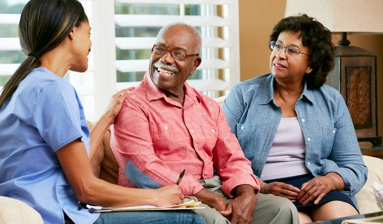 Caregiver sitting with a senior couple