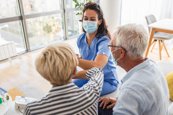 Caregiver with Mask giving elbow greeting