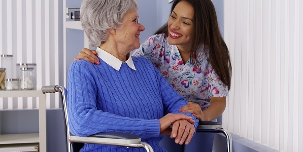 Senior in wheelchair with caregiver smiling and assisting