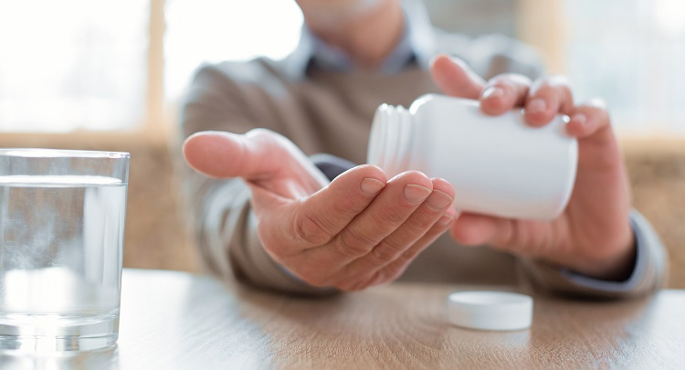 Close up of a senior male pouring medication into his hands