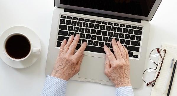Elderly hands on a laptop computer