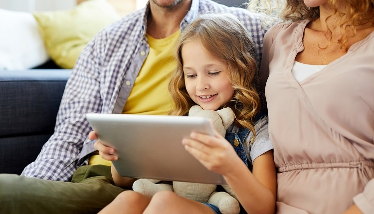 Cute, happy child on a tablet, sitting between her parents