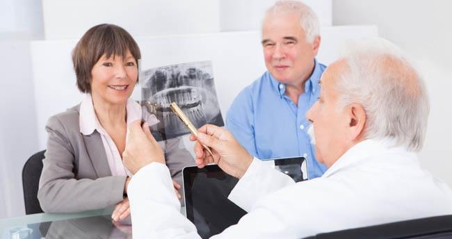 Dentist showing elderly couple Dental XRays