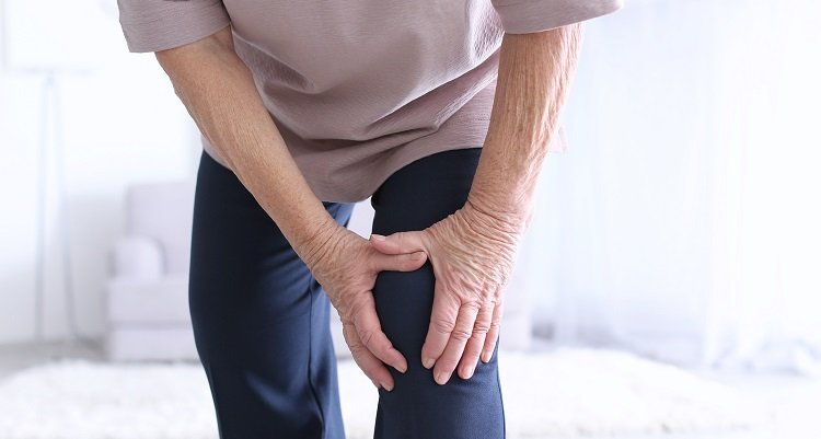Elderly woman holding her knee as if in pain
