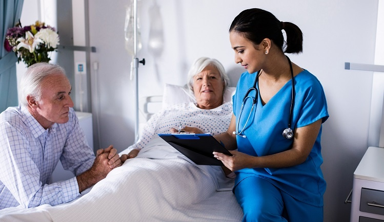 Female doctor discussing options with a senior couple in a hospital room