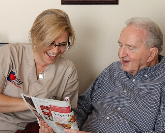 Caregiver and Elderly Man Reading