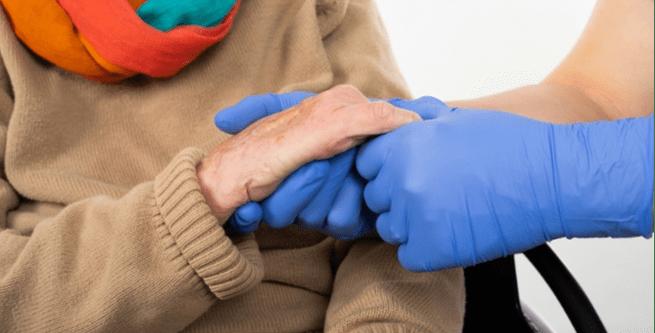 Gloved Caregiver Holding Hands Elderly Woman-1