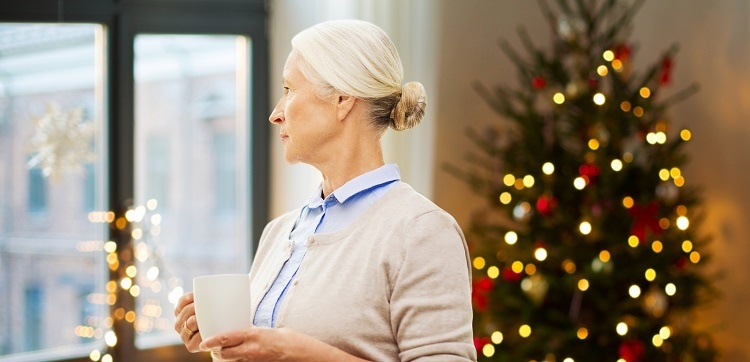 Lonely senior woman with a cup of tea looking through the window with Christmas lights in the background