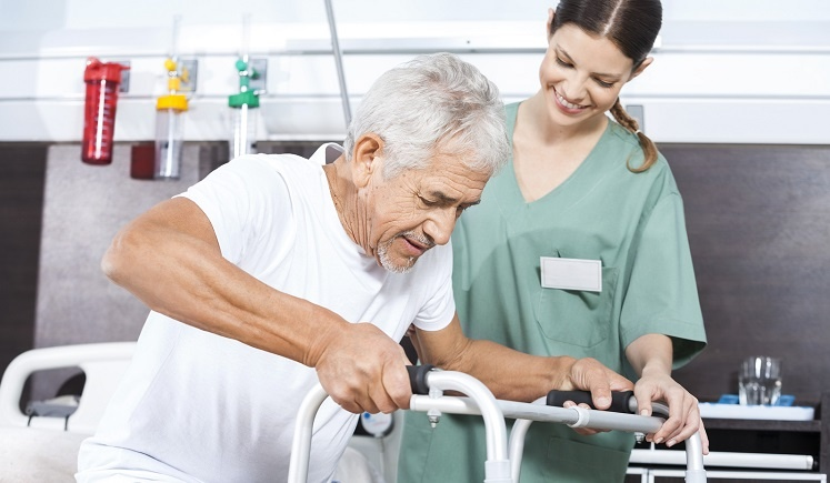 Senior male being assisted with a walker by a female nurse