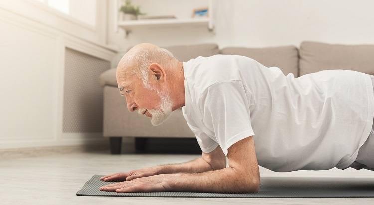 Senior man doing planks in his living room