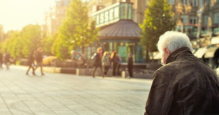 Senior man sitting on a bench outdoors LR