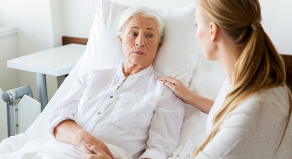 Senior woman in a hospital bed with a concerned look on her face; her daughter sits nearby