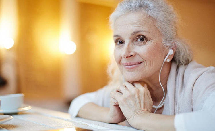 Senior woman listening to music with ear buds