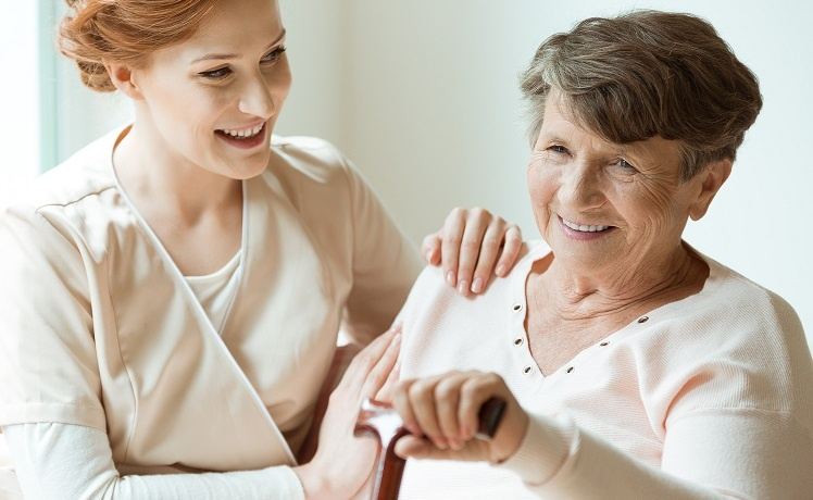 Young female caregiver sitting with an elderly woman holding a cane