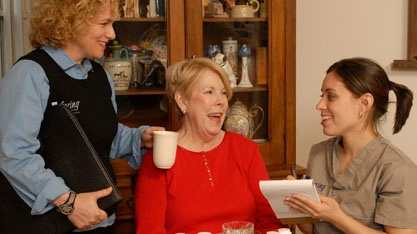 Caregiver and director laughing with resident