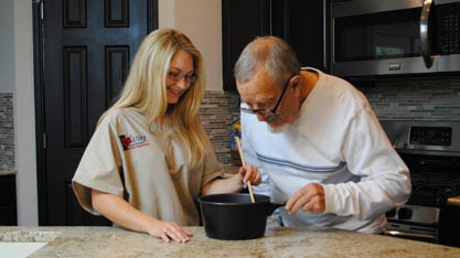 Caregiver cooking with elderly resident