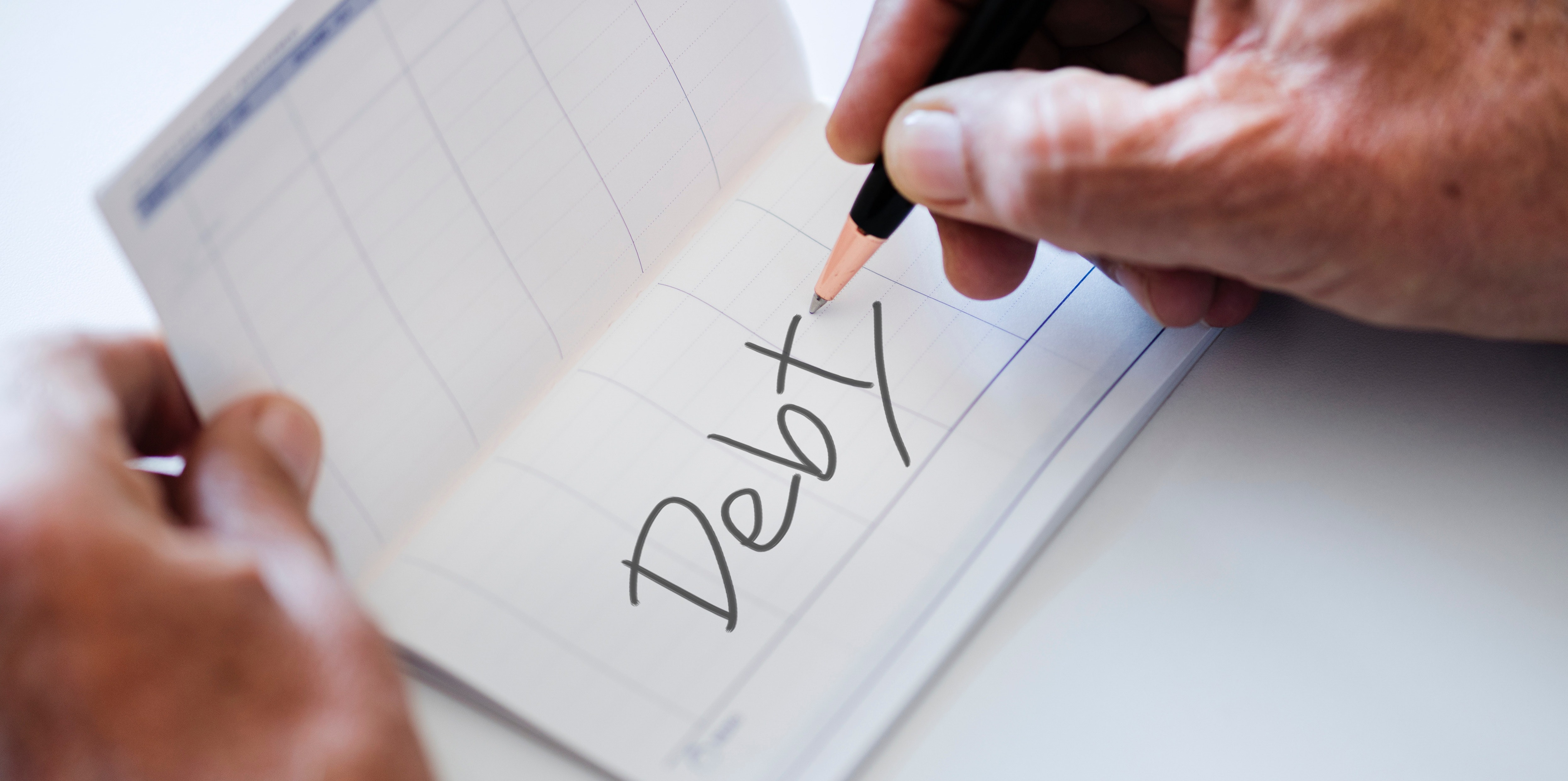 """Wrinkled hand writing """"debt"""" with a pen"""
