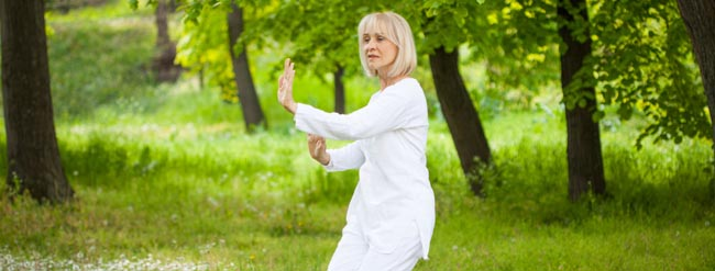 Senior woman doing tai chi outdoors