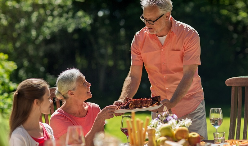 Senior man offering his wife a plat of ribs at an outdoor picnic