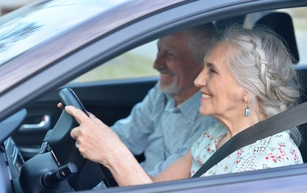 Senior woman driving a car with her husband in the passenger seat
