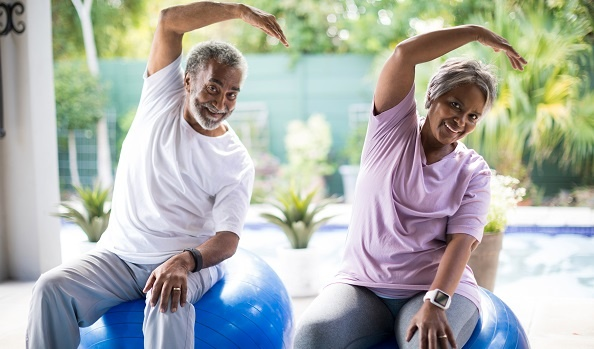 Senior couple working out on exercise balls