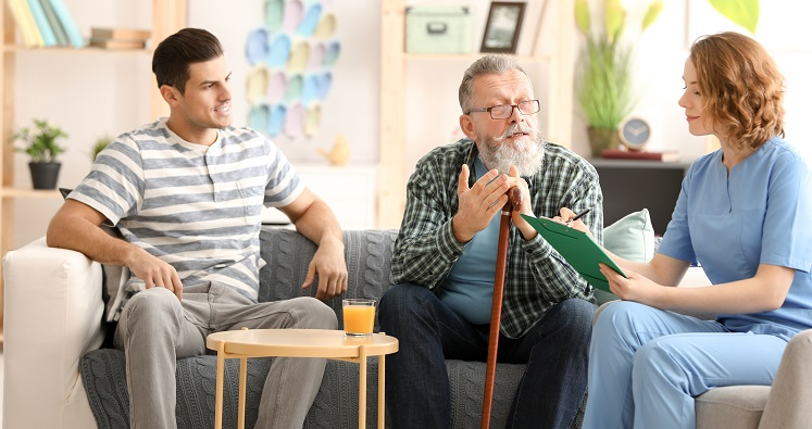 Caregiver with a senior man and his son at home