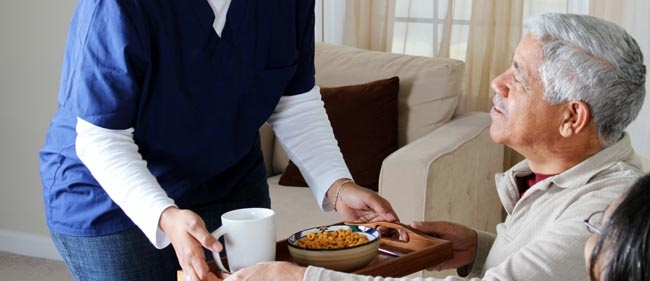 Caregiver serving senior male a tray of food