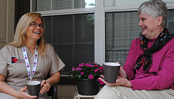 Caregiver and Elderly Woman Chatting on Porch
