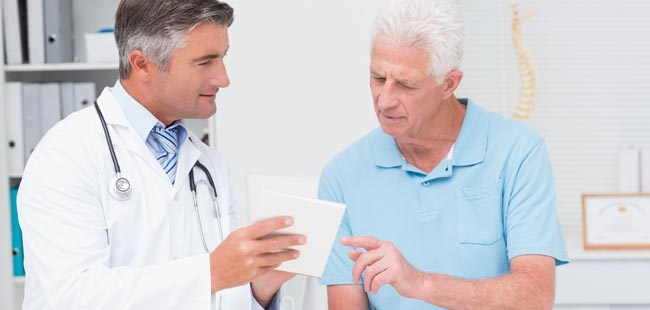 Doctor explaining prescription to elderly man