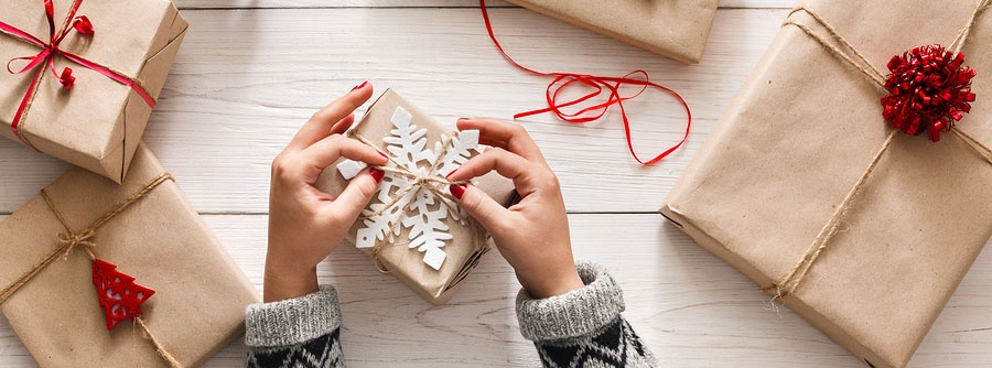Female hands tying a snowflake decoration on a Christmas present