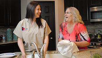 Caregiver Helping Senior Woman Wash Dishes