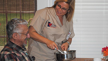 Caregiver Serving Elderly Man a Meal