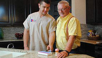 Caregiver Pointing to Pill Box for Elderly Man
