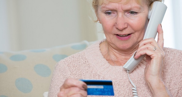 Senior woman calling with her credit card in hand