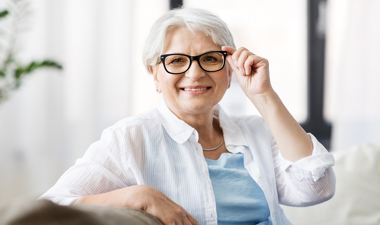 Senior woman holding glasses while sitting down
