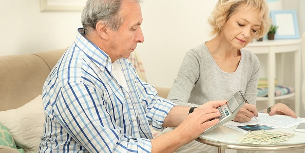 Senior couple with calculator doing taxes