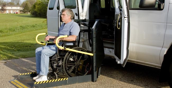 Senior on wheelchair lift getting out of van