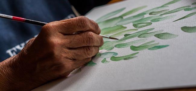 Elderly artist's hand painting
