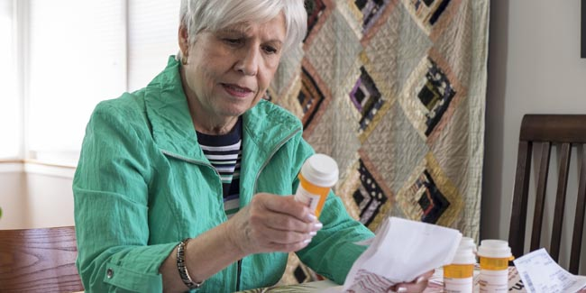 Senior lady reading prescription bottles