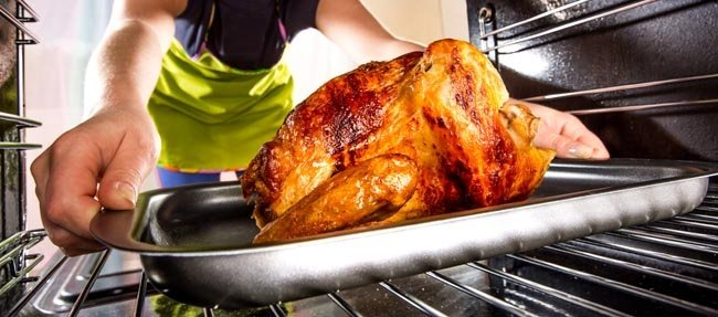Person putting roast chicken into oven